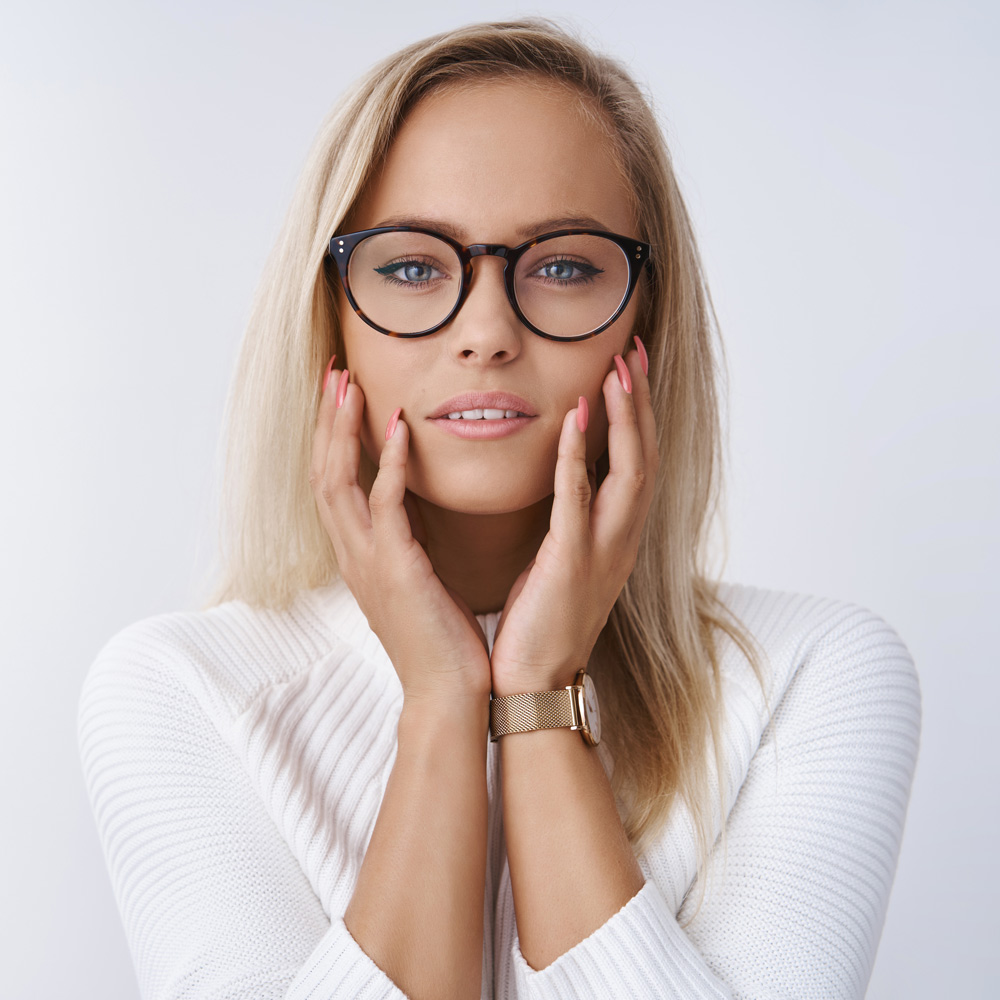 blonde woman touching her glasses