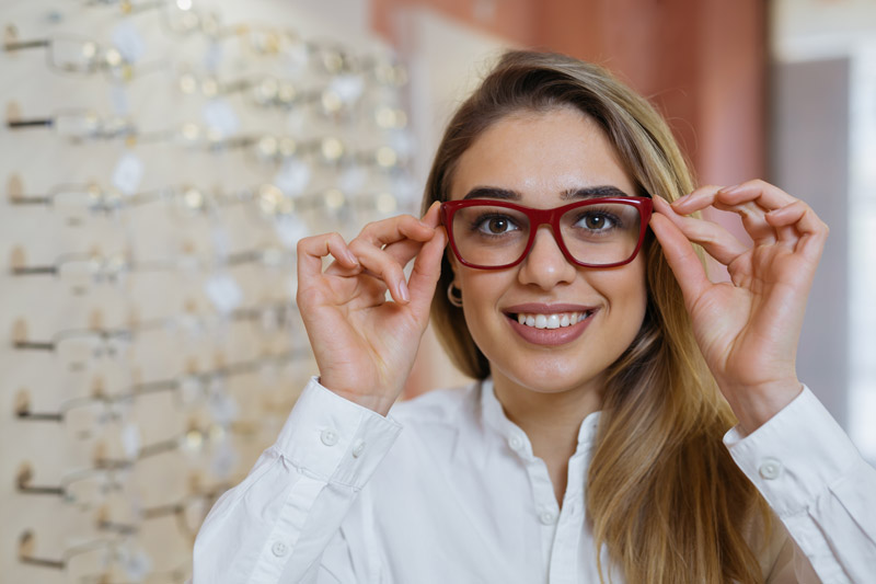 woman trying on red glasses in optical shop